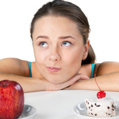 woman deciding between an apple or cake